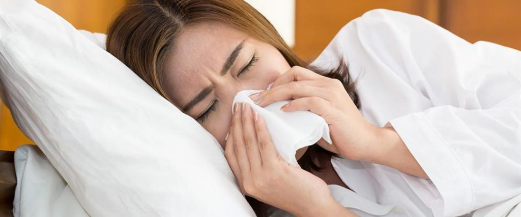 asian-woman-sneezing-in-a-tissue-on-bed